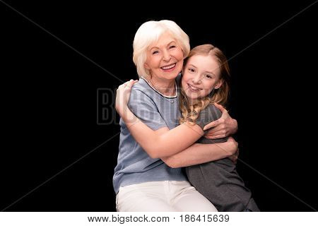 happy grandmother and granddaughter hugging each other isolated on black