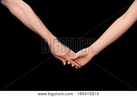 Close-up partial view of grandmother and grandchild holding hands isolated on black