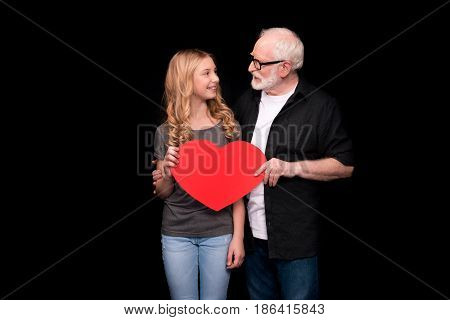 Happy grandfather and granddaughter holding red heart symbol and smiling each other