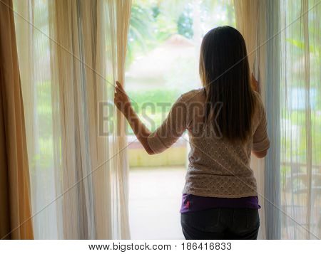 Rear view of a young woman holding the curtains open to look out of a large light window at home interior. Positive and aspirational lifestyle. Sad Woman looking out a window indoors.