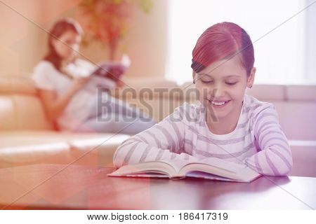 Smiling girl reading book with mother in background at home