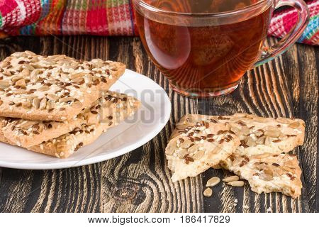 crispy bread with seeds of sunflower, flax and sesame seeds with a cup of tea on a dark wooden background.