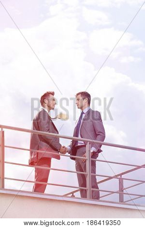 Side view of businessmen shaking hands at terrace railings against sky