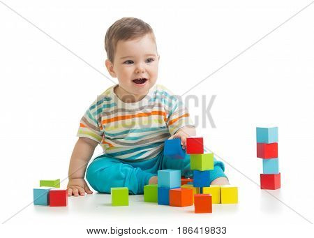 Baby boy building from toy blocks. Isolated on white background