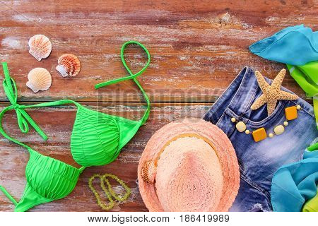 Summer women's clothing and accessories: hat, bathing suit, denim shorts, pareo, shells. Top view.