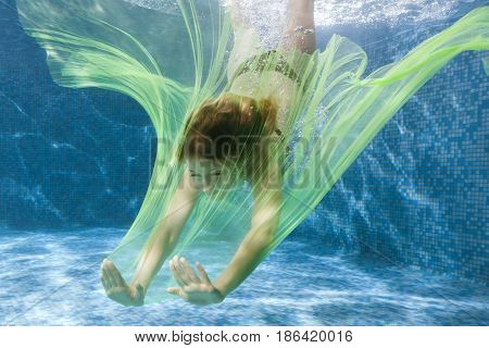 Woman dives with a fabric under the water in the pool.