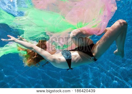 Woman in water has got confused in transparent fabric.