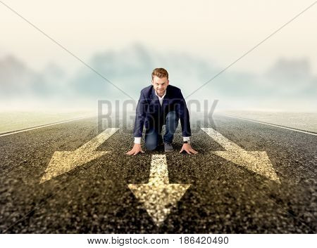Young determined businessman kneeling before three arrows