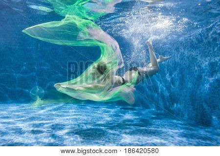 At the bottom of the pool a woman with a colored fabric dives.