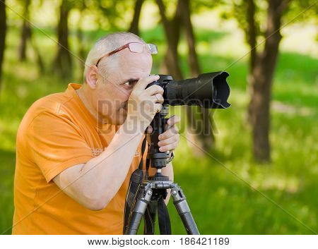 Enthusiastic mature photographer taking professional photo outdoor.