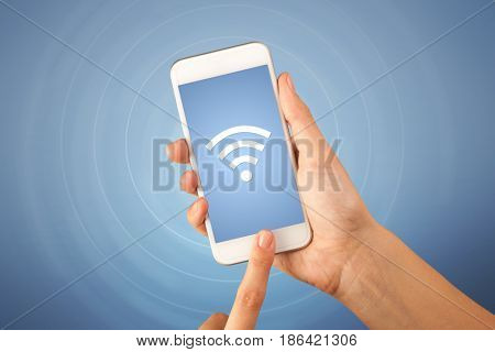 Female fingers touching smartphone with wireless connection icon