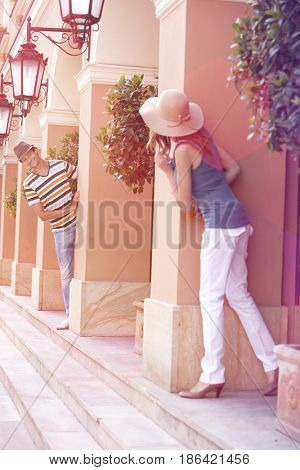 Tourist couple looking at each other while hiding behind columns