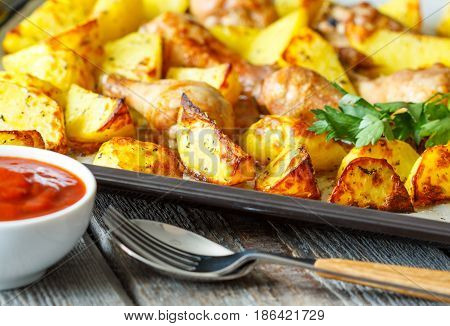 Baked potatoes with chicken on a baking sheet.