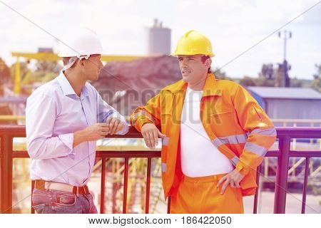 Architects standing against railing at construction site