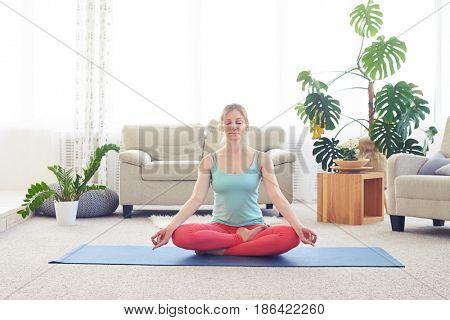 Wide shot of marvelous woman meditating in lotus asana on yoga mat