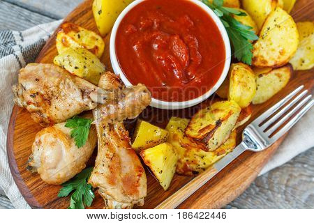 Baked potatoes with chicken and sauce on a wooden board.