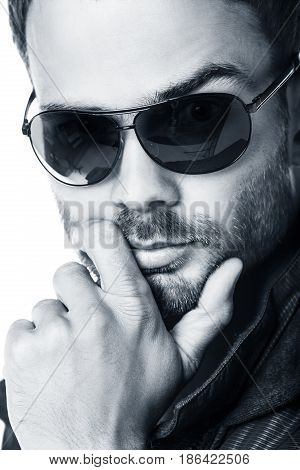 Close-up portrait of handsome young man in sunglasses over white background