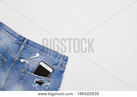 Top view of ripped shorts with telephone and headphones in pocket on white background. Place for copy space