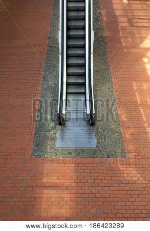 Escalator upward and brick tile floor on background