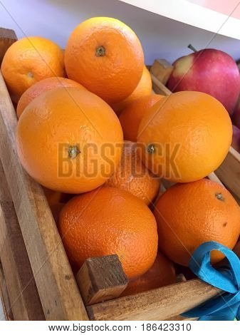 Fresh oranges in a wooden box in a store