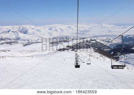 Empty cableway at winter day in Cahkadzor resort in mountains; Hrazdan town far away