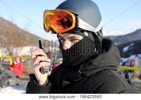 Boy with ski goggles saids on radio in ski resort at winter sunny day