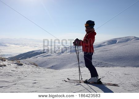 Girl in ski goggles srtands on top of mountain in ski resort at winter day