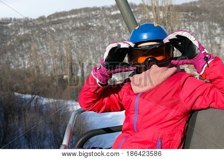 Happy girl in ski goggles looks away during lifting at cableway in ski resort at winter day