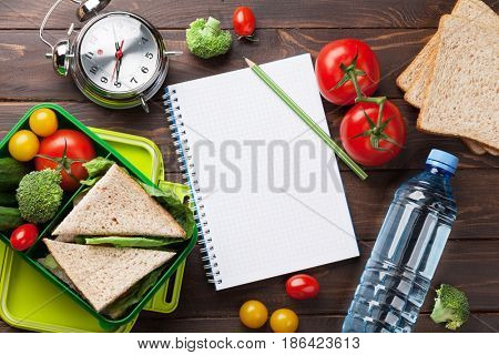 Lunch box with vegetables and sandwich and notepad on wooden table. Kids take away food box. Top view with space for your text