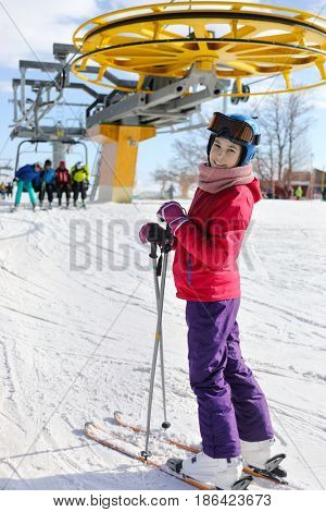 Girl with ski goggles smiles near modern cableway in ski resort at winter day