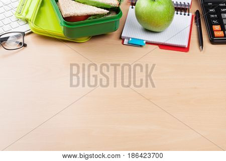 Office desk with supplies and lunch box with vegetables and sandwich. With copy space
