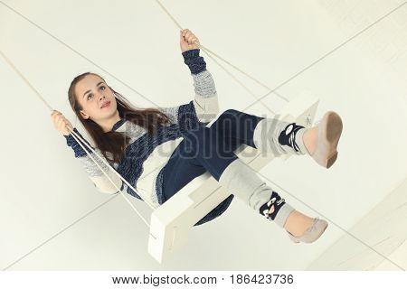 Happy girl teenager in jeans and gaiters swings in white studio and looks away