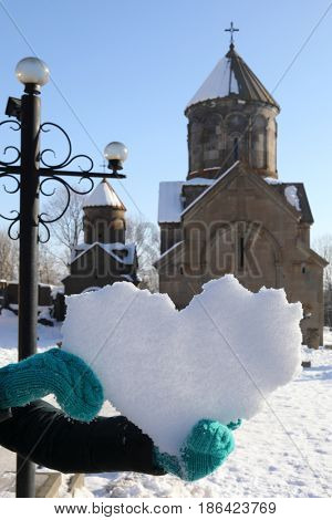 Hands hold snowy heart near Church in Sevanavank monastery at winter, it is ancient architectural monument of Armenia, 9th century