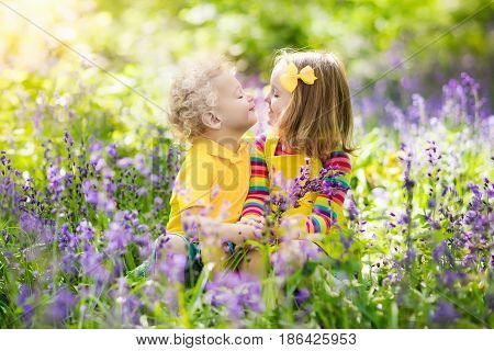 Kids Playing In Blooming Garden With Bluebell Flowers
