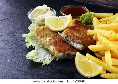 traditional British fish and chips on black background