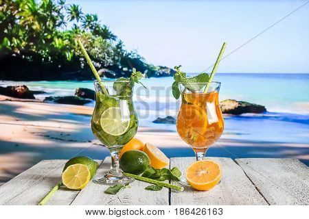 Fresh mojito cocktail on white wooden table with blue sea as a background.
