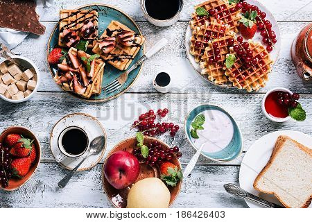 Breakfast table with waffles, yogurt, coffee and fresh fruits and berries on white wooden background, top view