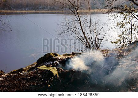 Cooking on the fire, the trip to Northern nature of the river. Food and rest for the wild outdoorsmen. Dining stop for a meal in tourism. Cooking on the wild nature tourists.