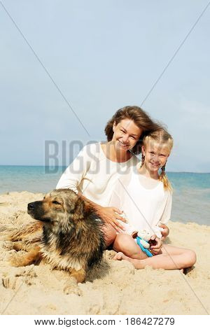 Happy family with dog on the beach