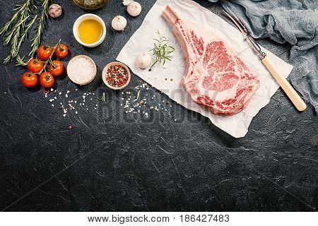 Raw tomahawk beef steak with ingredients for grilling: seasoning, fresh rosemary and olive oil on paper over black background, top view