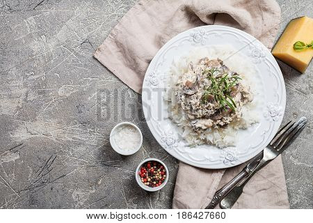 rice with mushrooms in a cream sauce on gray background, top view with copy space