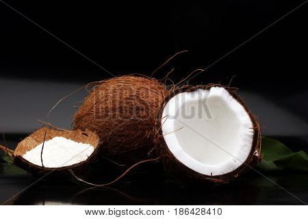 Coconut and half coco on glossy black background