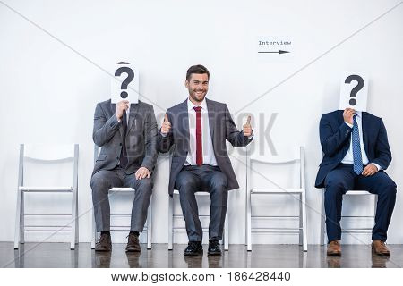 Businesspeople Sitting In Queue And Waiting For Interview, Holding Question Marks In Office, Busines