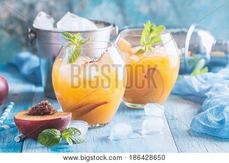 Peach cocktail or tea with ice and mint on blue background.