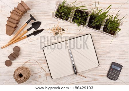 Gardening tools, blank daily log with pen, peat tablets and pots and young seedlings on a wooden background. Concept of spring gardening. Top view with copy space.