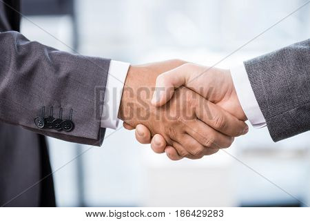 Close-up Partial View Of Two Businessmen In Formal Wear Shaking Hands, Business Concept
