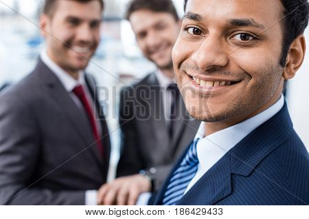Close-up portrait of smiling african american businessman looking at camera with colleagues standing behind business concept