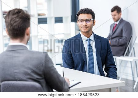 Young businessmen in formal wear sitting and talking at job interview in office business concept