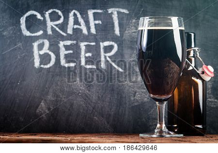 Glass of dark beer with bottle on a chalk board background