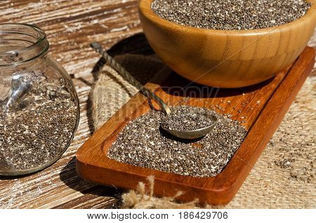 Close up of spoon with chia seeds (Salvia hispanica) on wooden plate. This superfood is a rich in omega-3 fatty acids essential for good health. Healthy eating vegan diet concept.